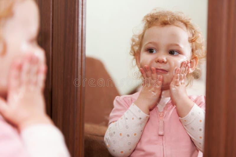 Bambino sveglio che applica crema sulle sue guance fotografia stock