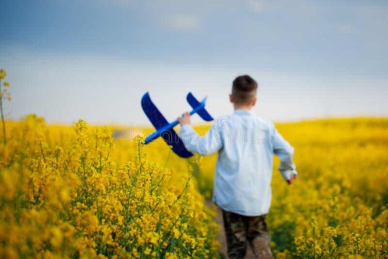 Bambino sveglio che cammina nel campo giallo un giorno di estate soleggiato Il ragazzo avvia l'aereo di carta Sfuocatura e fuoco  fotografie stock libere da diritti