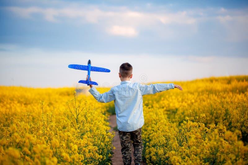Bambino sveglio che cammina nel campo giallo un giorno di estate soleggiato Il ragazzo avvia l'aereo di carta Vista posteriore fotografia stock libera da diritti