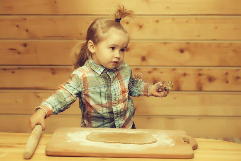 Bambino sveglio che cucina con la pasta e la farina, muffa metallica delle tenute immagine stock