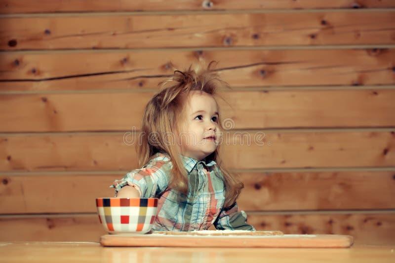 Bambino sveglio che cucina con la pasta, la farina e la ciotola su legno fotografia stock libera da diritti