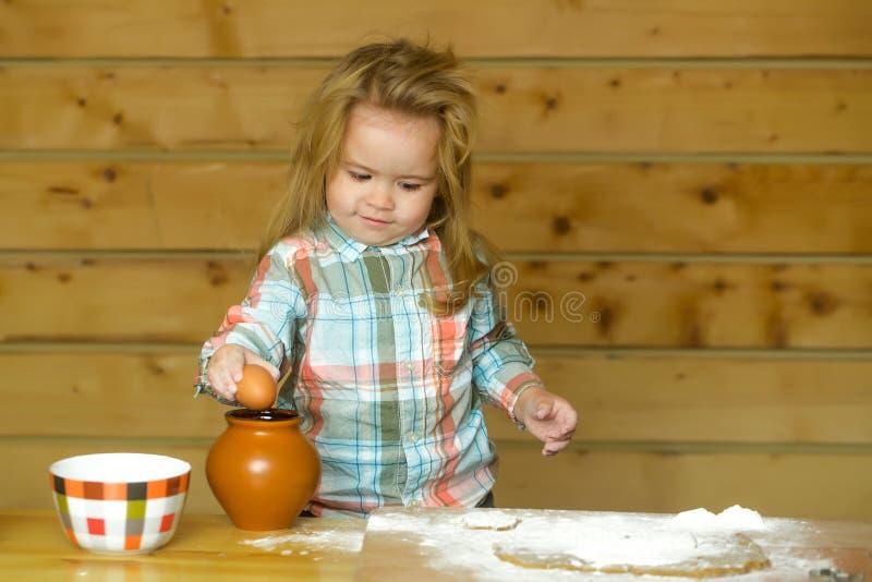 Bambino sveglio che cucina con la pasta, la farina, l'uovo e la ciotola immagine stock libera da diritti