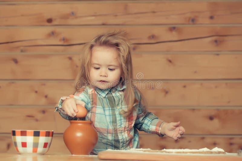 Bambino sveglio che cucina con la pasta, la farina, l'uovo e la ciotola fotografie stock