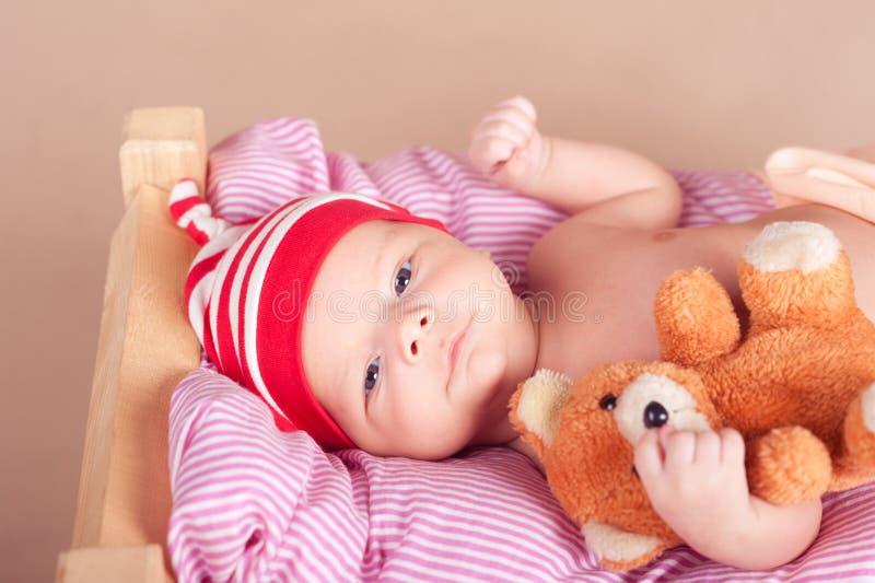 Bambino sveglio che dorme a letto con l'orsacchiotto fotografia stock libera da diritti