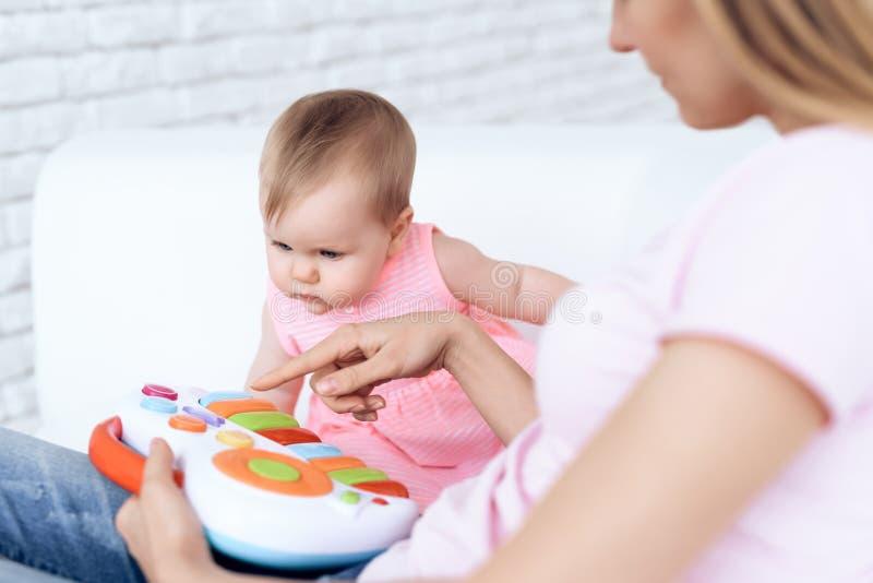 Bambino sveglio che gioca giocattolo sul sofà con la madre fotografia stock