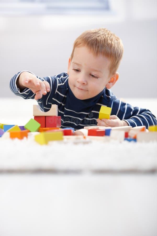 Bambino sveglio che gioca sul pavimento nel paese fotografie stock libere da diritti