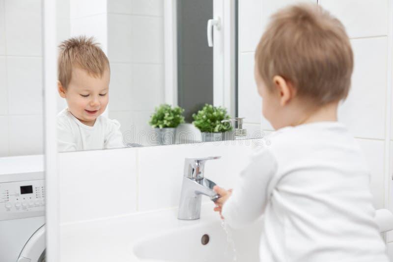 Bambino sveglio che impara come lavare il suo fronte fotografia stock libera da diritti