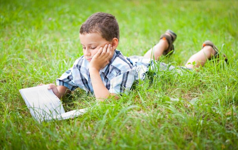 Bambino sveglio che legge un libro esterno immagini stock libere da diritti