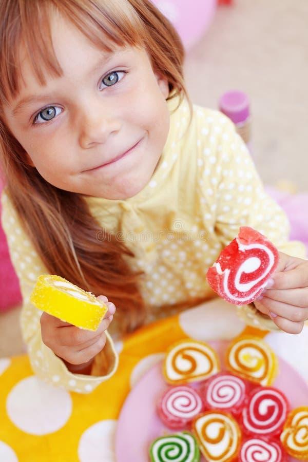 Bambino sveglio che mangia le caramelle fotografia stock