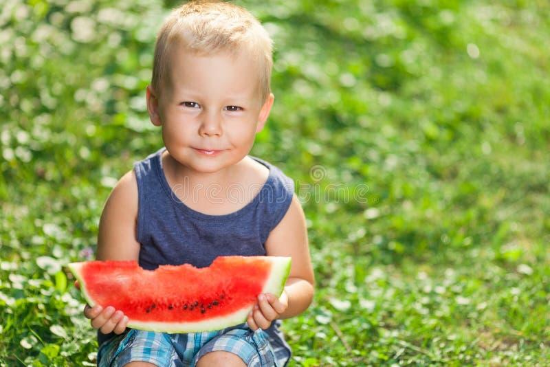 Bambino sveglio che mangia una fetta di anguria immagine stock