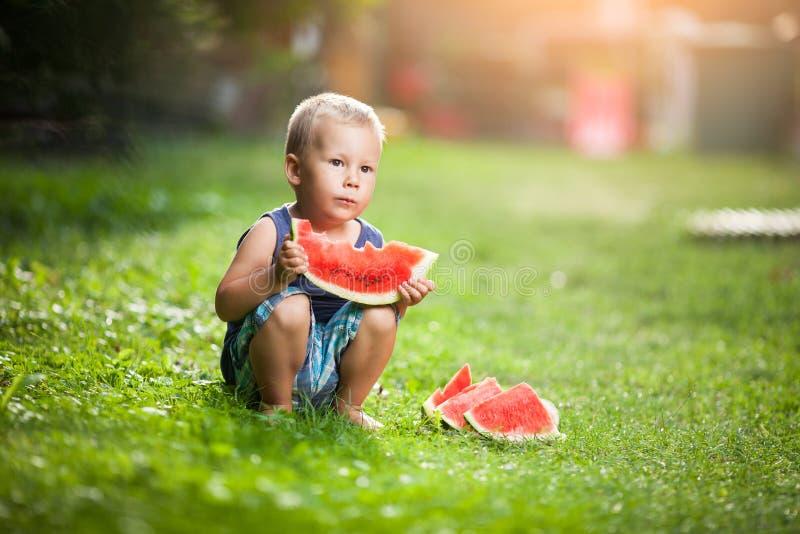 Bambino sveglio che mangia una fetta di anguria immagini stock libere da diritti