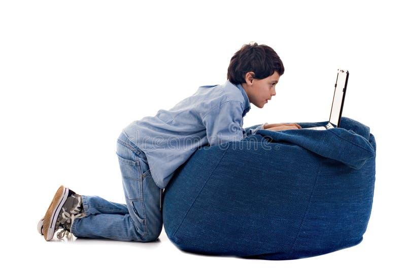 Bambino sveglio che per mezzo di un computer portatile fotografie stock libere da diritti