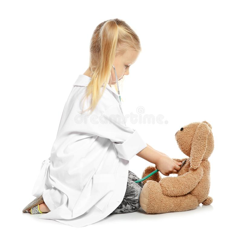 Bambino sveglio che si immagina come medico mentre giocando con il coniglietto del giocattolo e dello stetoscopio su fondo bianco immagine stock libera da diritti