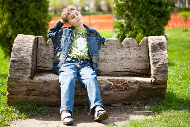 Bambino sveglio che si siede sul banco immagini stock libere da diritti