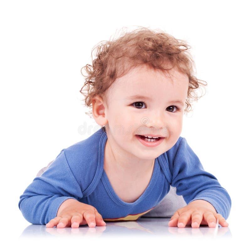 Bambino sveglio che si trova sulla sulla sue pancia e risata fotografie stock libere da diritti