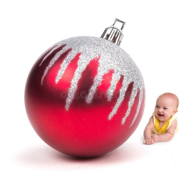 Bambino sveglio che sorride ad un ornamento enorme di Natale su bianco immagine stock