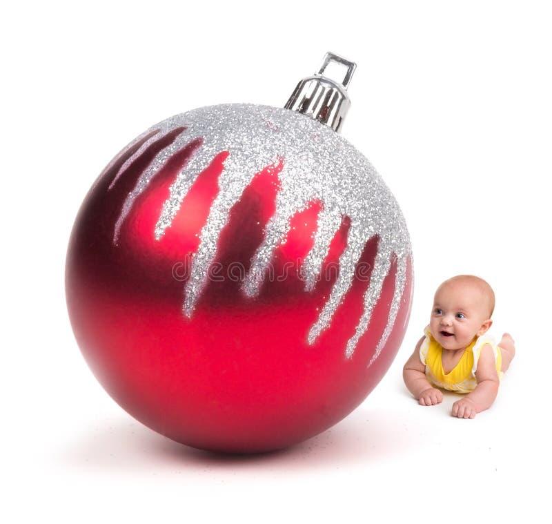 Bambino sveglio che sorride ad un ornamento enorme di Natale su bianco fotografia stock