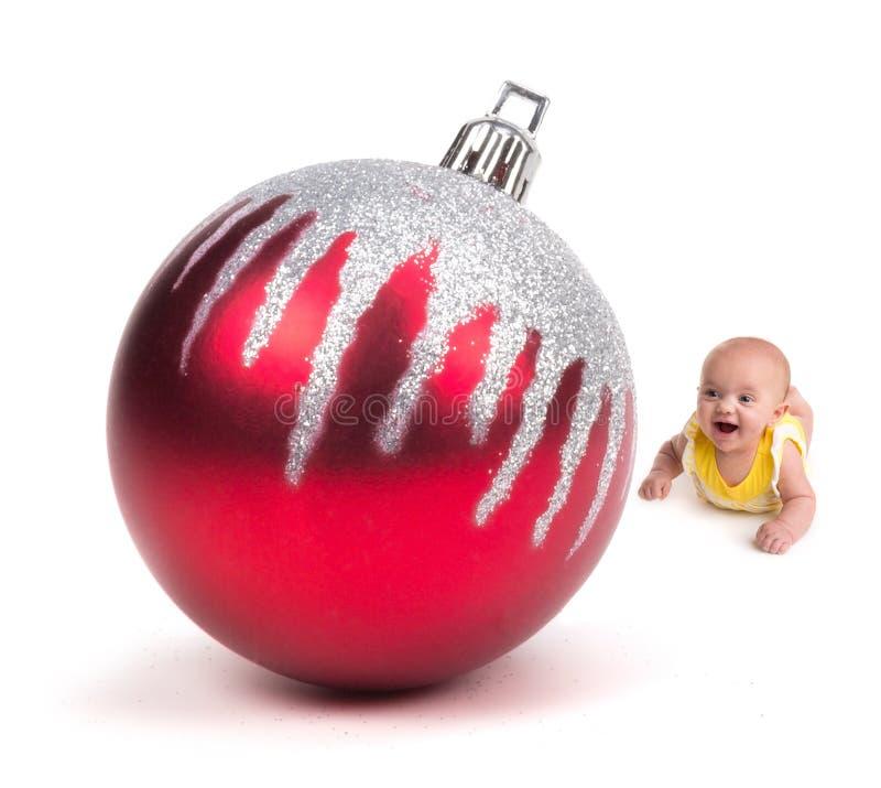 Bambino sveglio che sorride ad un ornamento enorme di Natale su bianco immagini stock