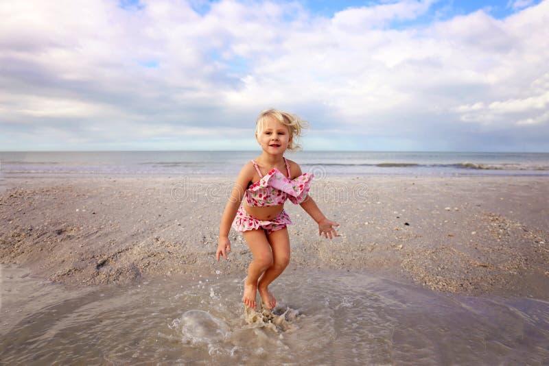 Bambino sveglio che spruzza e che gioca nell'acqua sulla spiaggia dall'oceano fotografia stock