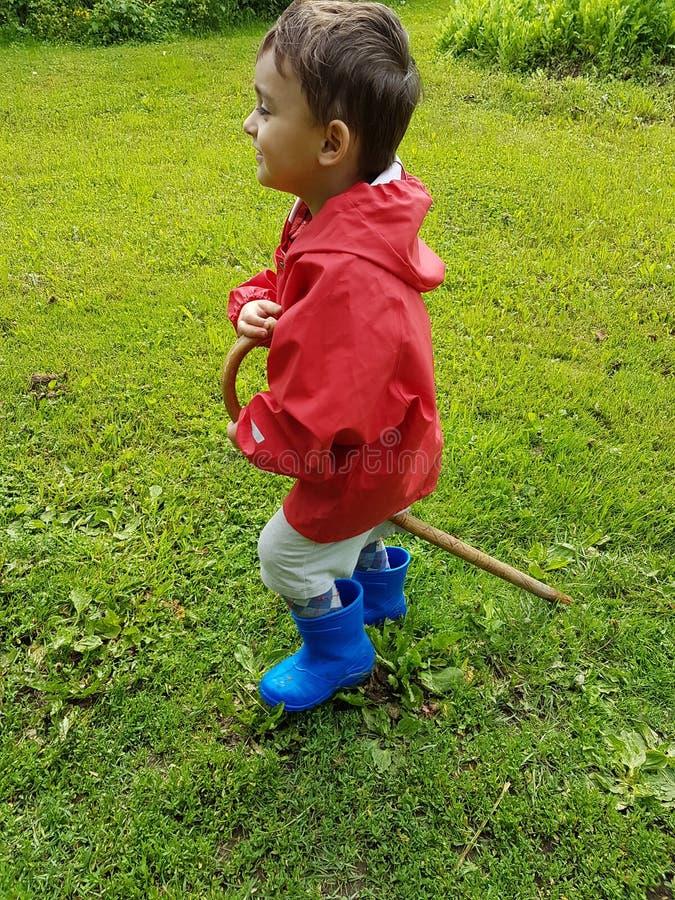 Bambino sveglio che sta sul prato con gli stivali di pioggia blu ed il rivestimento rosso della pioggia immagini stock libere da diritti