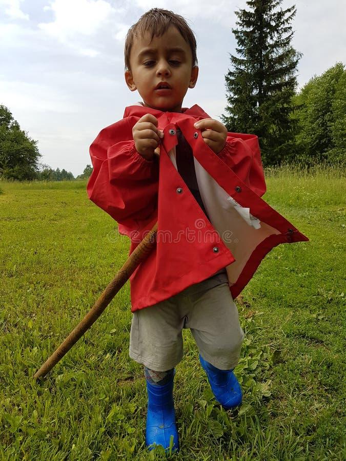 Bambino sveglio che sta sul prato con gli stivali di pioggia blu ed il rivestimento rosso della pioggia fotografie stock libere da diritti