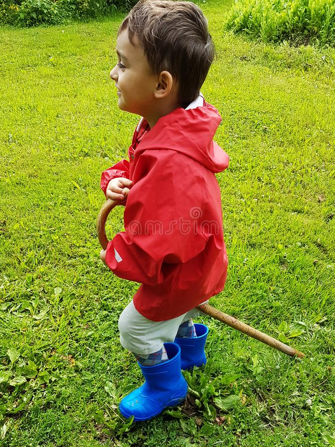 Bambino sveglio che sta sul prato con gli stivali di pioggia blu ed il rivestimento rosso della pioggia fotografia stock libera da diritti