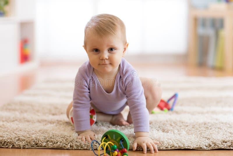 Bambino sveglio che striscia sul pavimento nella stanza della scuola materna immagine stock