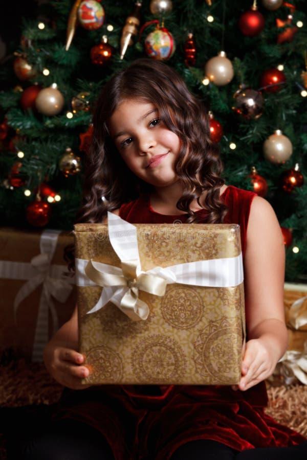 Bambino sveglio che tiene un regalo avvolto immagine stock