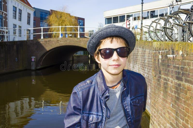 Bambino sveglio con gli occhiali da sole ed il cappello in un ambiente urbano fotografie stock libere da diritti