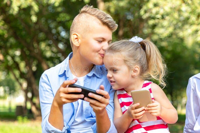 Bambino sveglio con i telefoni che si siedono fuori e che per mezzo di un aggeggio - fratello che bacia sua sorella sulla guancia fotografie stock libere da diritti