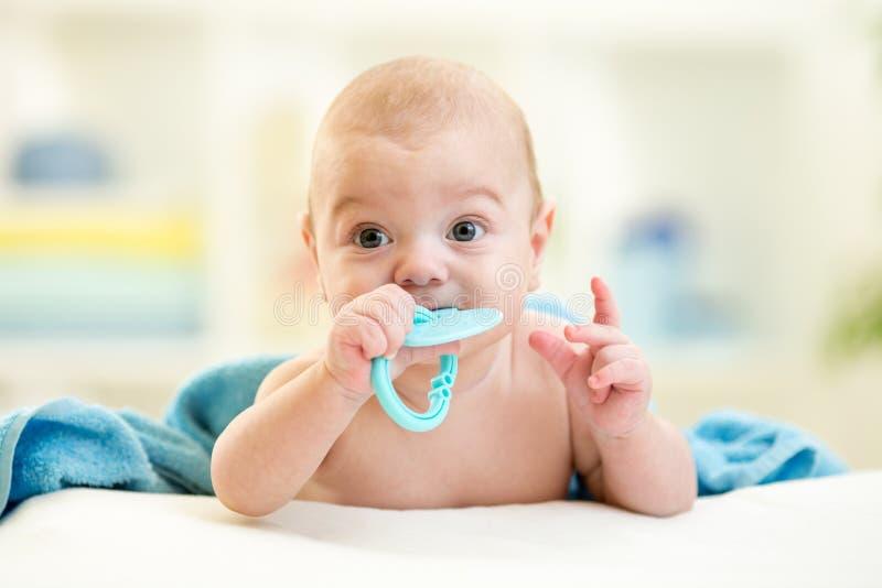 Bambino sveglio con il giocattolo del teether dopo il bagno fotografia stock