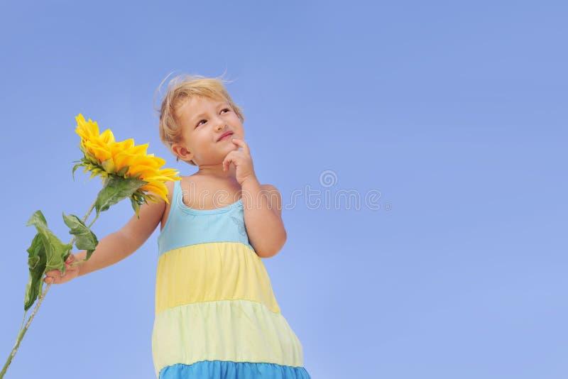 Bambino sveglio con il girasole che esamina lo spazio della copia immagini stock libere da diritti