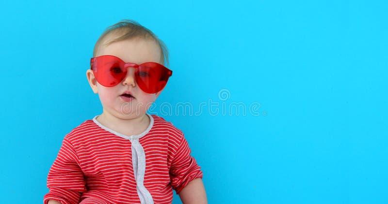 Bambino sveglio con il bambino in occhiali da sole rossi fotografie stock