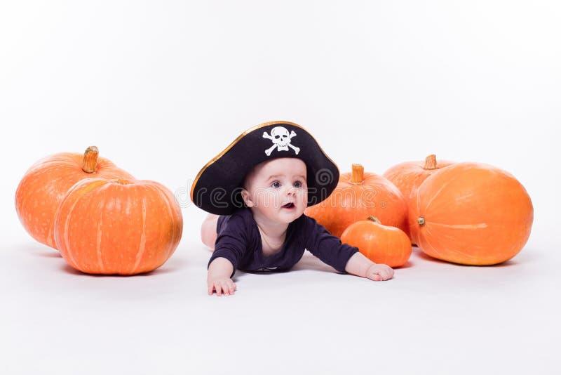 Bambino sveglio con un cappello del pirata sulla sua testa che si trova sul suo stomaco sopra fotografia stock libera da diritti