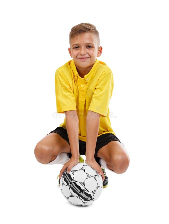 Bambino sveglio con un pallone da calcio isolato su un fondo bianco Calcio della scuola Strumentazione di sport L'attivo mette in fotografia stock libera da diritti