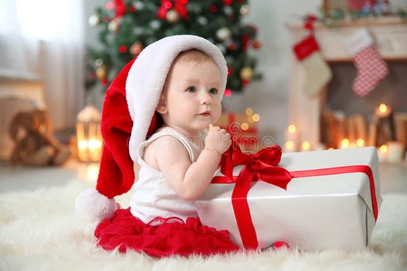 Bambino sveglio in contenitore di regalo di apertura del cappello di Santa a casa fotografia stock libera da diritti