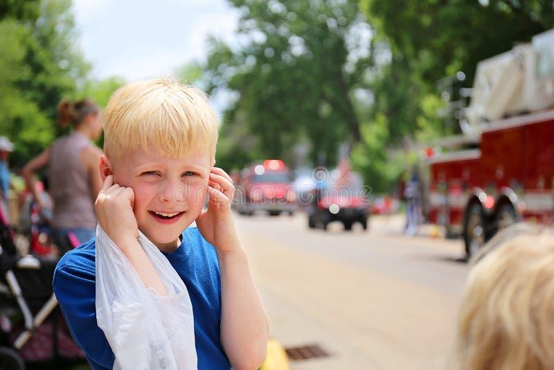 Bambino sveglio del ragazzo alla parata che tappa le sue orecchie dalle sirene rumorose del camion dei vigili del fuoco fotografie stock libere da diritti