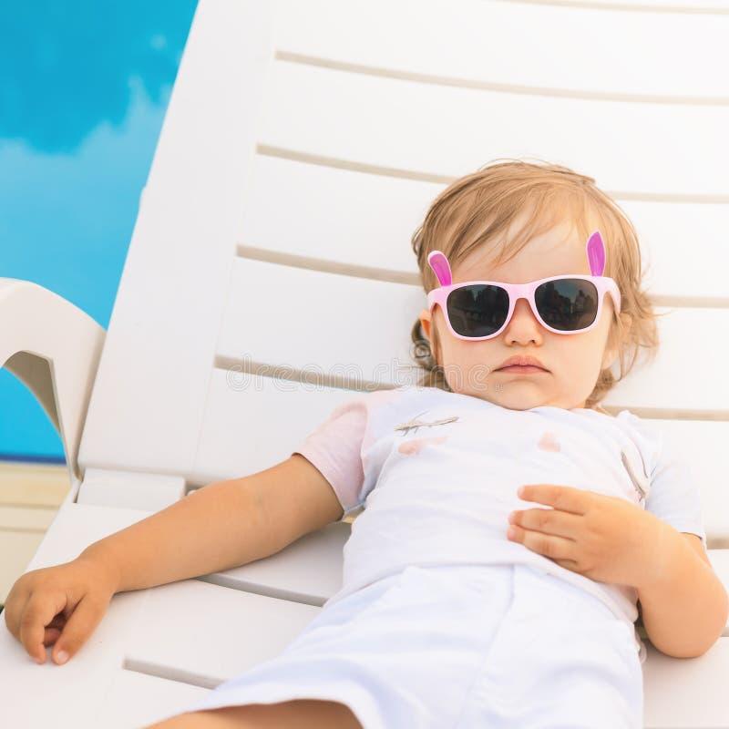 Bambino sveglio di estate senza fine che si rilassa al lettino vicino allo stagno, località di soggiorno immagine stock libera da diritti