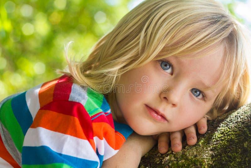 Bambino sveglio e felice che si rilassa in profondità nel pensiero all'aperto immagini stock libere da diritti