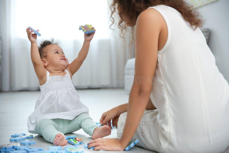 Bambino sveglio e giovane gioco della madre fotografia stock libera da diritti
