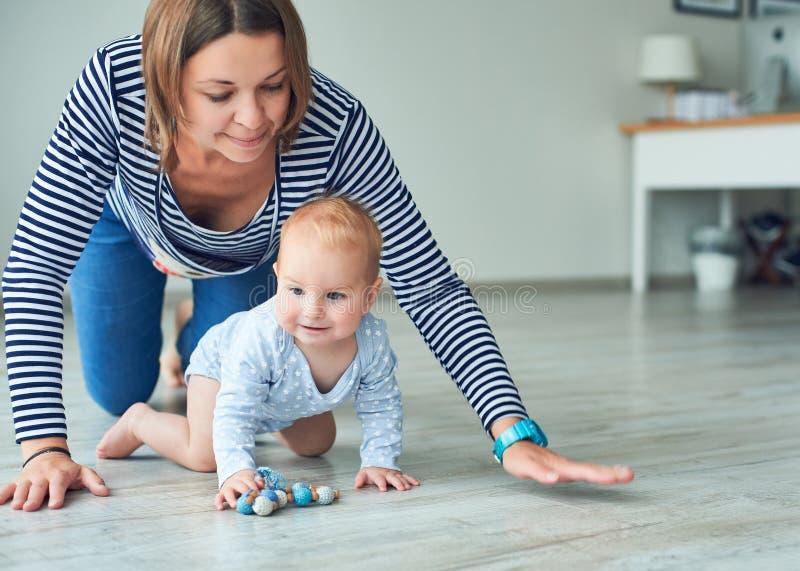 Bambino sveglio e giovane madre che strisciano a casa fotografia stock libera da diritti
