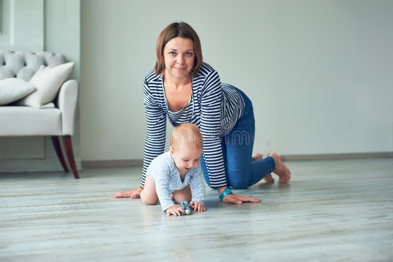 Bambino sveglio e giovane madre che strisciano a casa fotografie stock libere da diritti