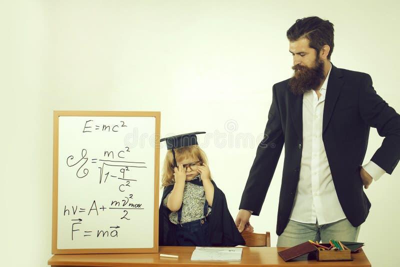 Bambino sveglio ed insegnante barbuto immagini stock