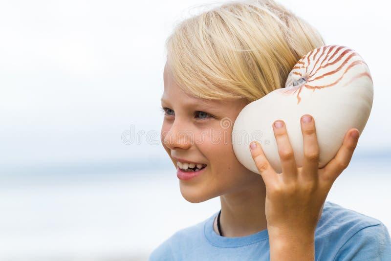 Download Bambino Sveglio Felice Che Ascolta Il Mare Nelle Coperture Di Nautilus Immagine Stock - Immagine di caucasico, orecchio: 56890225