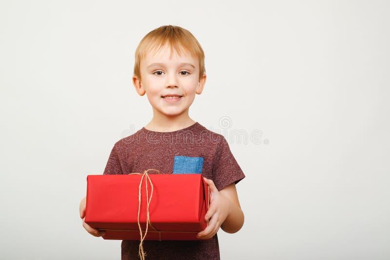 Bambino sveglio felice che giudica il contenitore di regalo rosso isolato sopra fondo bianco fotografie stock libere da diritti