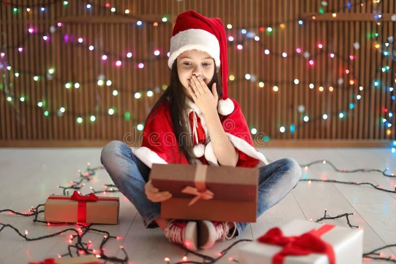 Bambino sveglio in regalo di Natale di apertura del cappello di Santa sul fondo vago delle luci fotografia stock