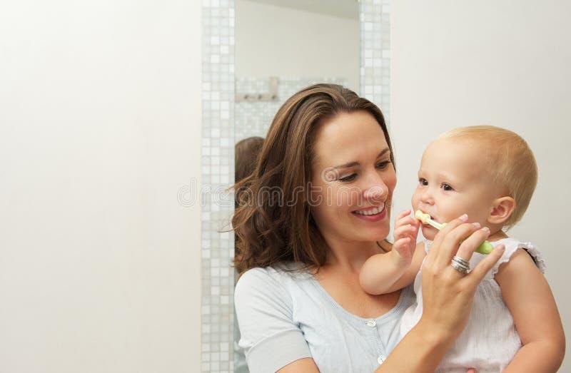 A bambino sveglio sorridente della madre insegnando a come pulire i denti con lo spazzolino da denti fotografia stock