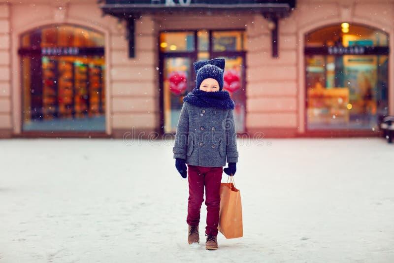 Bambino sveglio su acquisto nella stagione invernale immagine stock