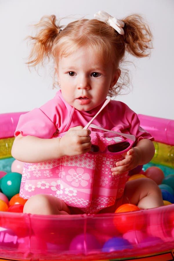 Bambino sveglio in un costume da bagno protettivo del galleggiante fotografie stock