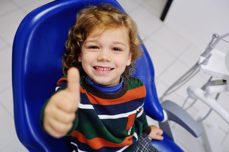 Bambino sveglio in un maglione a strisce al ricevimento al dentista fotografia stock